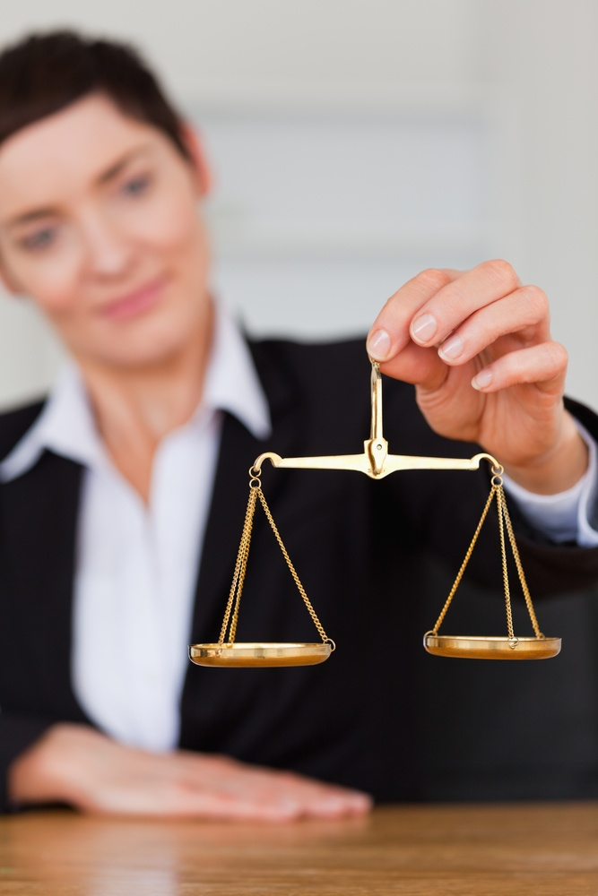 Serious woman holding the justice scale in her office-1